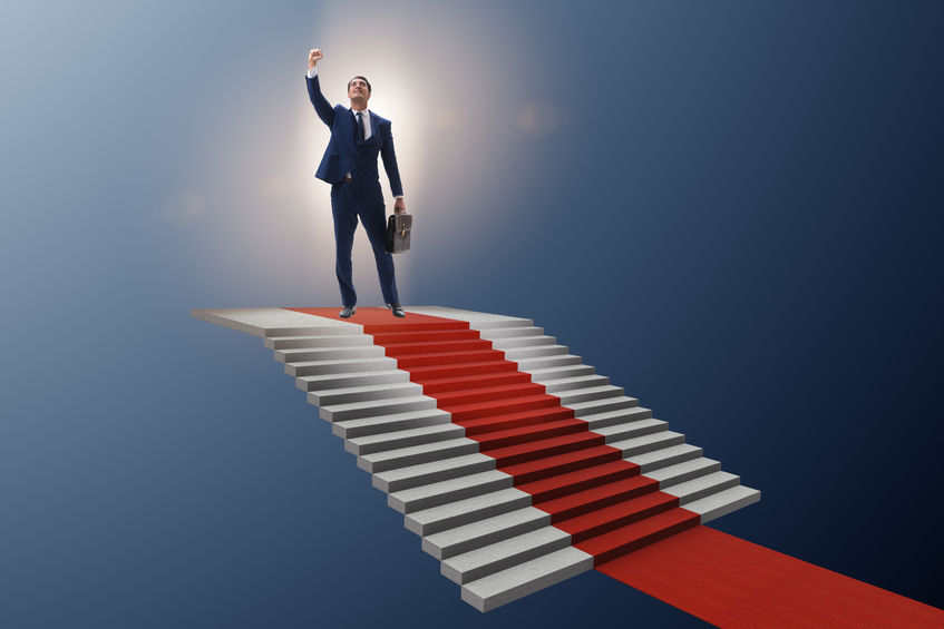 95065049 - young businessman climbing stairs and red carpet